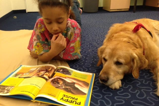 Alexandra Gamble shares a story with her canine pal, Dusty, during the 'Paws to Read' program at the Hohenfels library.