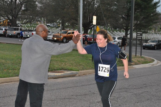 Anne-Marie Guthrie gives Cpl. Terry L. Smith Gym Facility Manager Cliff Holcomb a high-five during the final yards of the Spring Salute 5k, which began and ended at Henderson Hall's Smith Gymnasium April 2. Guthrie finished the Joint Base Myer-Henderson Hall road race in exactly 30 minutes.