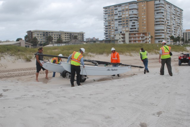 Employees from Broward County, U.S. Army Corps of Engineers and Eastman Aggregate help a resident to relocate his catamaran from the beach to facilitate sand placement.  A united team effort contributed to making the Broward County beach renourishment project a success.