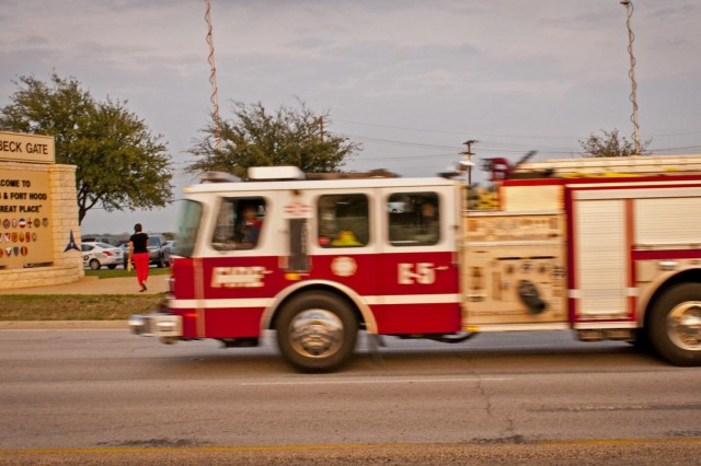 A fire truck rushes onto Fort Hood past reporters setting up for a press conference in front of the main gate after a shooting on the base April 2, 2014. (U.S. Army photo by Sgt. Ken Scar, 7th Mobile Public Affairs Detachment)