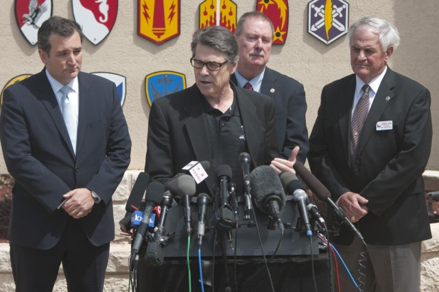 Texas Gov. Rick Perry answers questions during a press conference in front of the Fort Hood main gate sign April 4, 2014. Perry and Sen. Ted Cruz (left) held the conference to address the April 2 shooting on the base. (U.S. Army photo by Sgt. Ken Scar, 7th Mobile Public Affairs Detachment)