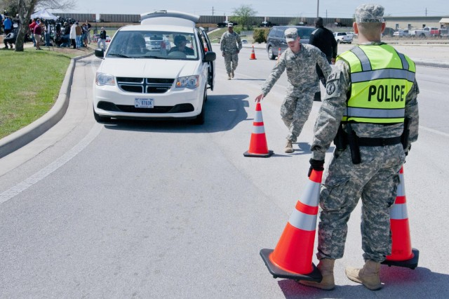 U.S. Army Soldiers with the Fort Hood military police block off a lane of the main road into the base April 4, 2014. (U.S. Army photo by Sgt. Ken Scar, 7th MPAD)