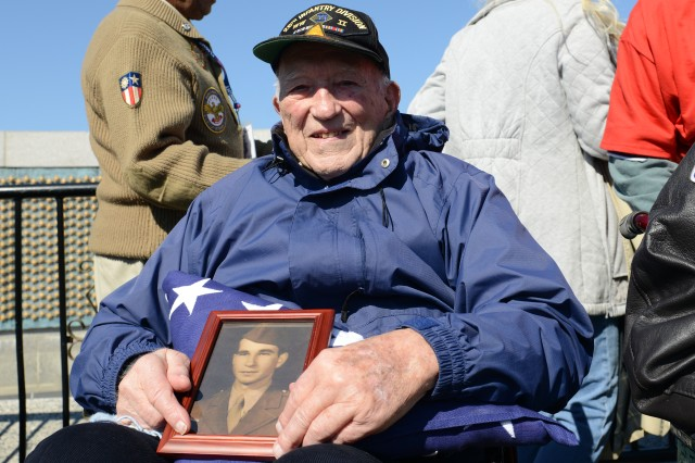 Army veteran Hugh Phelps holds a picture of his brother Patrick, an Army veteran, on his lap atop a folded American flag, as he visited the World War II Memorial in Washington, D.C., April 5, 2014.
