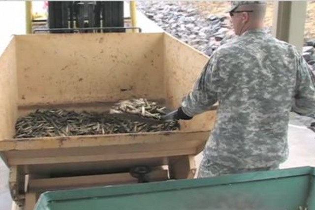1st Sgt. Chad Turner is shown feeding recycled brass into the safety certification unit. Approximately 60 tons were treated and subsequently recycled in 2013.  Ammunition Supply Point personnel assume responsibility for operating the unit.