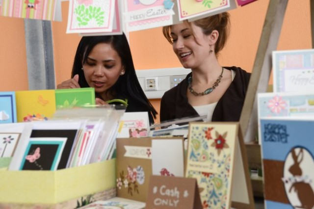 """From left: Krystelle Chaney and Kendra Buttner of """"The Paper Dolls"""" create homemade greeting cards during last year's Arts and Craft Fair, a spouses' club event."""