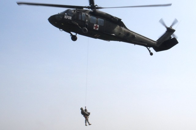 Staff Sgt. Josh Rose, a military dog handler with the 131st Military Working Dog Detachment and non-commissioned officer-in-charge of Camp Bondsteel's dog kennel, is hoisted up to a hovering UH-60 Black Hawk helicopter with his dog, Bumper, at Camp Bondsteel, April 2, 2014.