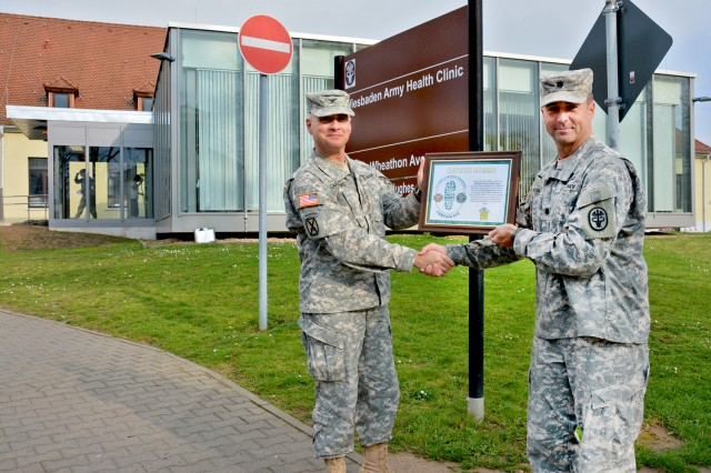 Col. David Carstens, U.S. Army Garrison Wiesbaden commander, presents Lt. Col. Michael Hughes, Wiesbaden Health Clinic commander, with the garrison's Green Boot Certificate.