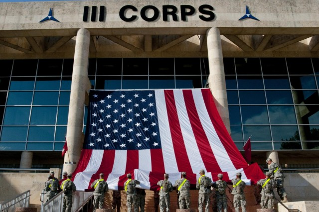U.S. Army Soldiers with the 1st Cavalry Division hang an American flag from the III Corps headquarters building on Fort Hood in preparation for a memorial service honoring the victims of the April 2 shooting on the base, April 7, 2014. President Barack Obama and first lady Michelle Obama are scheduled to attend the April 9 ceremony. (U.S. Army photo by Sgt. Ken Scar, 7th Mobile Public Affairs Detachment)