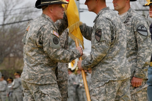 "Brig. Gen. Michael Bills (left), commander of the 1st Cavalry Division, receives the Ironhorse colors from Col. Steve Gilland, the outgoing commander of the 1st �""Ironhorse"" Brigade Combat Team, 1st Cavalry Division, at the Ironhorse change of command and assumption of responsibility ceremony April 7 at Fort Hood, Texas. The passing of the colors is a tradition signifying the responsibility associated with the command. Gilland passing the colors to Bills signified returning the responsibility he was entrusted upon assuming command. (U.S. Army photo by Spc. Paige Behringer, 1BCT PAO, 1st Cav. Div.)"