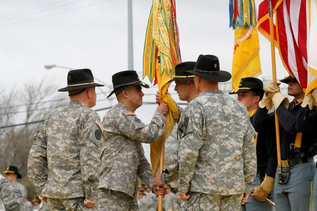 "Col. John DiGiambattista (center), the incoming commander of the 1st �""Ironhorse"" Brigade Combat Team, 1st Cavalry Division, hands the brigade colors to Command Sgt. Maj. Joseph Cornelison (center, right), the incoming senior noncommissioned officer, at the Ironhorse change of command and assumption of responsibility ceremony April 7 at Fort Hood, Texas. The passing of the colors is a tradition signifying the responsibility associated with the command. (U.S. Army photo by Spc. Paige Behringer, 1BCT PAO, 1st Cav. Div.)"
