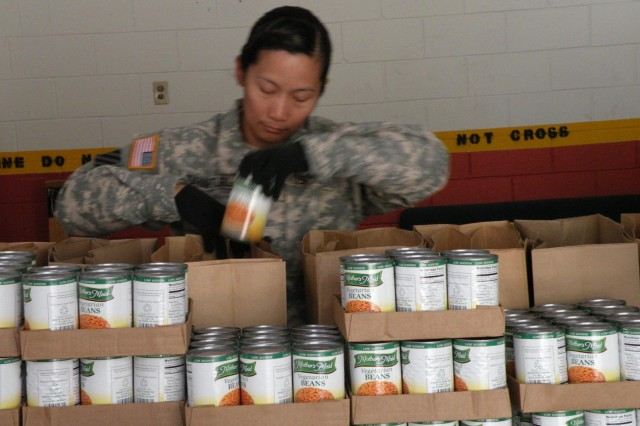 Spc. Abigail Tayagturla, a member of the Distribution Platoon from Company E, 703rd Brigade Support Battalion, attached to 3rd Battalion, 15th Infantry Regiment, 4th Infantry Brigade Combat Team, 3rd Infantry Division, bags food for families in need in Waltourville, Ga., March 27, 2014. Soldiers, firefighters, and other members of the community joined to help package and distribute food in support of the United Way Mass Mobile Food Drop.
