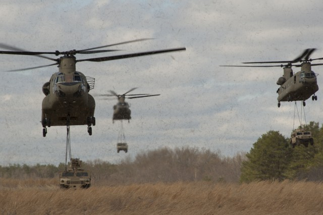 "CH-47F Chinook helicopters from 6th Battalion, 101st Combat Aviation Brigade ""Wings of Destiny,"" transport Humvees from the 3rd Battalion, 187th Infantry Regiment, 3rd Brigade Combat Team ""Rakkasans,"" 101st Airborne Division (Air Assault), into Landing Zone Red Crow during the full dress rehearsal for Operation Golden Eagle at Fort Campbell, Ky., April 4, 2014. The four-day exercise was the first brigade-size air assault operation conducted by the 101st Airborne Division in more than a decade, and featured Soldiers from 3rd Brigade Combat Team and 101st Combat Aviation Brigade moving more than 1,100 Soldiers and sling-loading more than 20 pieces of equipment."