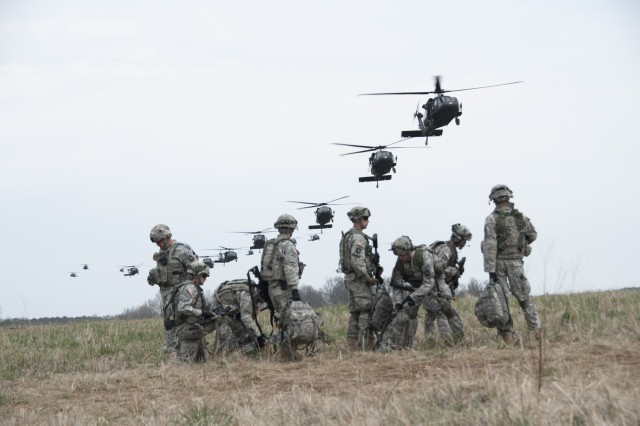 """Soldiers from 3rd Brigade Combat Team """"Rakkasans,"""" 101st Airborne Division (Air Assault), watch a flight of UH-60 Black Hawk helicopters from 5th Battalion, 101st Combat Aviation Brigade """"Wings of Destiny,"""" as they return to Pickup Zone Cardinal to load more Soldiers during Operation Golden Eagle at Fort Campbell, Ky., April 8, 2014. The four-day exercise was the first brigade-size air assault operation conducted by the 101st Airborne Division in more than a decade, and featured Soldiers from 3rd Brigade Combat Team and 101st Combat Aviation Brigade moving more than 1,100 Soldiers and sling-loading more than 20 pieces of equipment."""