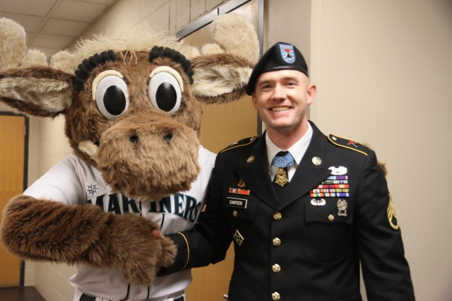 U.S. Army Staff Sgt. Ty Carter, a Medal of Honor recipient, meets Seattle Mariners mascot Mariner Moose, during a baseball game between the Seattle Mariners and Los Angeles Angels Tuesday, April 8, 2014, in Seattle.