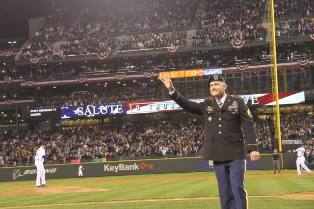 U.S. Army Staff Sgt. Ty Carter, a Medal of Honor recipient, waves to fans while being honored during a baseball game between the Seattle Mariners and Los Angeles Angels Tuesday, April 8, 2014, in Seattle. Carter is currently assigned to 7th Infantry Division, Joint Base Lewis-McChord, Wash.