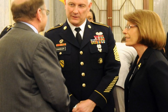 Sgt. Maj. of the Army Ray Chandler (center) and his wife Jeanne speak to Gary Leeling, general counsel for the Senate Armed Services Committee, during a break in the Personnel Subcommittee's hearing on Capitol Hill, April 9, 2014.  Chandler and his service counterparts provided testimony related to quality of life issues.