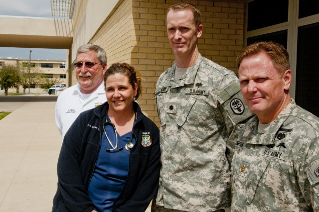 From left: Frederick Reed, Fort Hood Emergency Medical Services chief; Dawn O'Connell, Carl R. Darnall Army Medical Center triage and charge nurse; Lt. Col. (Dr.) James Lucas, Carl R. Darnell chief of the Department of Surgery; and Maj. (Dr.) Michael Simpson, Carl R. Darnell ER officer-in-charge, stand next to the emergency bay in which ambulances delivered the casualties from the April 2, 2014, shooting on Fort Hood, Texas. All four pictured here and their teams treated every casualty hurt in the incident, in many cases saving lives with only minutes to spare. Four people were killed and 16 injured in the tragedy.