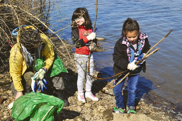 Left to right: Gale Bernatz, troop leader for Girl Scout Daisy Troop 1444 (out of Rose, Hill, Va.) looks on as Robin Bernatz, 6, and Marisol Larios, 6, pick up an old rope to throw away during Fort Belvoir's Potomac River Watershed Cleanup Sunday.