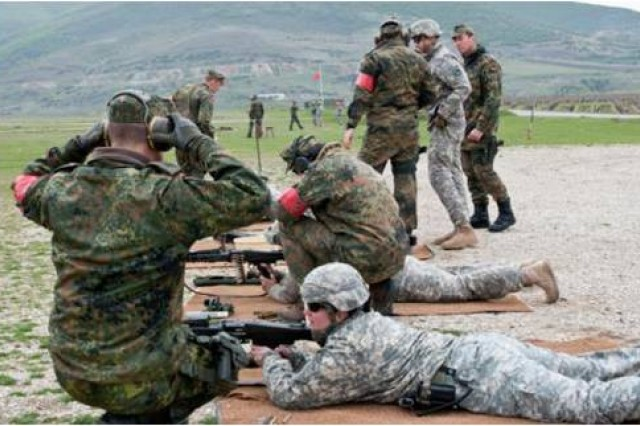 U.S. and German soldiers fire weapons during the German marksmanship range near Orahovac, Kosovo, April 7. Multinational events like the Schutzenschnur range and the Danish Contingency march gives U.S. Soldiers a chance to bond with multinational partners on a personal level.