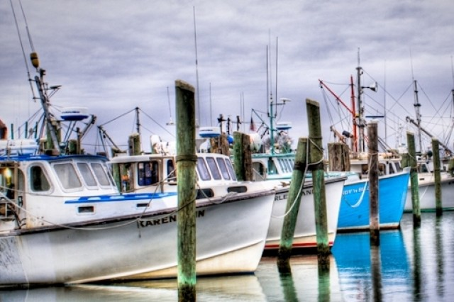 Fishing pier and small commercial fishing vessels moored at Point Judith Harbor, R.I.