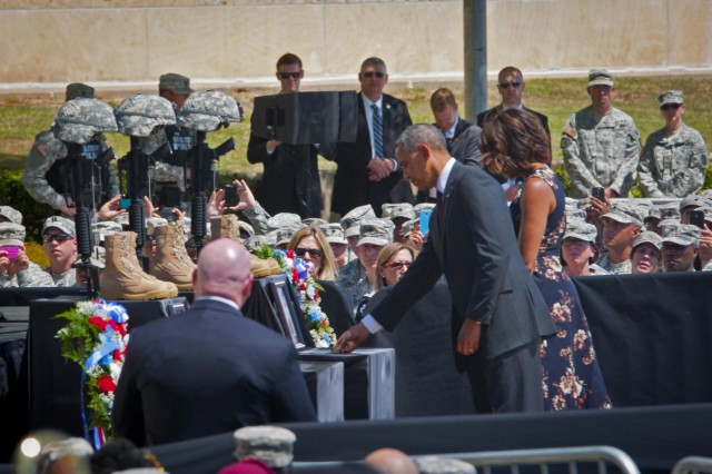 President Barack Obama and first lady Michelle Obama pay their respects during a memorial service for Sgt. 1st Class Daniel M. Ferguson, Staff Sgt. Carlos A. Lazaney-Rodriguez, and Sgt. Timothy W. Owens, who were killed in the April 2 shooting tragedy on Fort Hood, April 9, 2014. (U.S. Army photo by Sgt. Ken Scar, 7th Mobile Public Affairs Detachment)