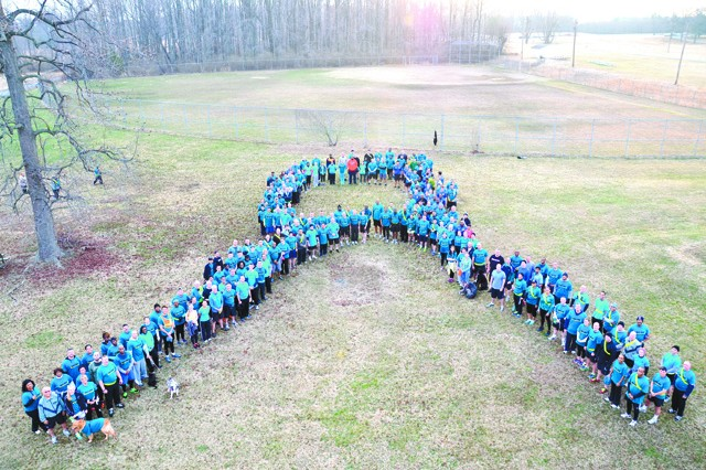 Runners form a human ribbon at CAPA Field in APG South (Edgewood) April 3 after the APG Sexual Assault Awareness Month (SAAM) Kickoff 5K Run to demonstrate Team APG's unity and commitment to preventing and combating sexual harassment and assault.  Most participants wore teal, the color associated with sexual assault, as determined by the National Violence Resource Center.