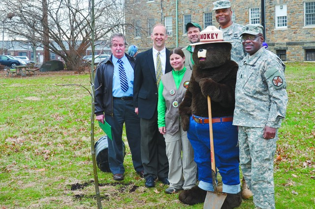 Wayne Merkel, a forester from the Maryland Department of Natural Resources Forest Service, APG Garrison Deputy Glenn Wait, Jessica Baylor and John Wrobel from DPW's Environmental Division, Smokey the Bear, Garrison Commander Col. Gregory McClinton and Garrison Command Sgt. Maj. James Ervin pose together after planting a seedling in the Garrison garden during an April 2 Arbor Day observance.