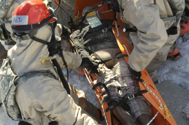 Members of the Oregon National Guard's CBRNE Enhanced Response Force Package (CERFP), free a simulated victim who was trapped during the Vigilant Guard-Alaska 2014 exercise, near Joint Base Elmendorf-Richardson, Anchorage, Alaska, March 29, 2014.