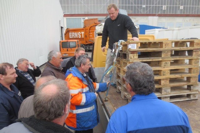 Ehrenfield Dengler, in orange and blue coat, inspects the straps securing a stack of pallets, assessing the work of Andreas Gackstatter, standing on the flatbed, a mason with the U.S. Army Garrison Ansbach Directorate of Public Works, who secured the pallets April 10, 2014. USAG Ansbach held a load securement class April 8 through 10 to train vehicle operators and equipment loaders on how to properly contain, immobilize and secure cargo.