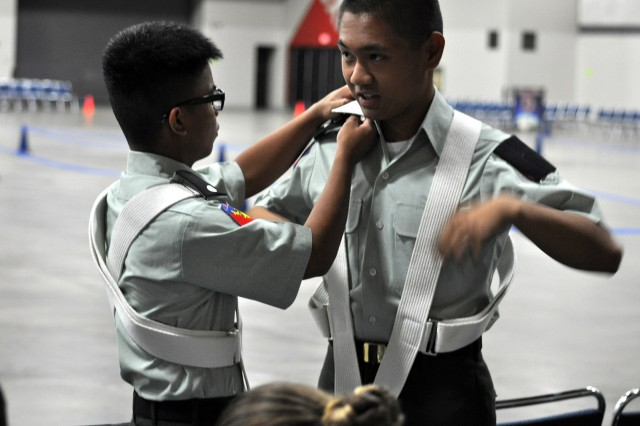 Cadet Jomari Sears (left), drill team commander for Waianae (Hawaii) High School, helps Cadet Christian Stephens prepare for the team?'s color guard inspection at the Army JROTC National Drill Classic held in Louisville, Ky., April 5.