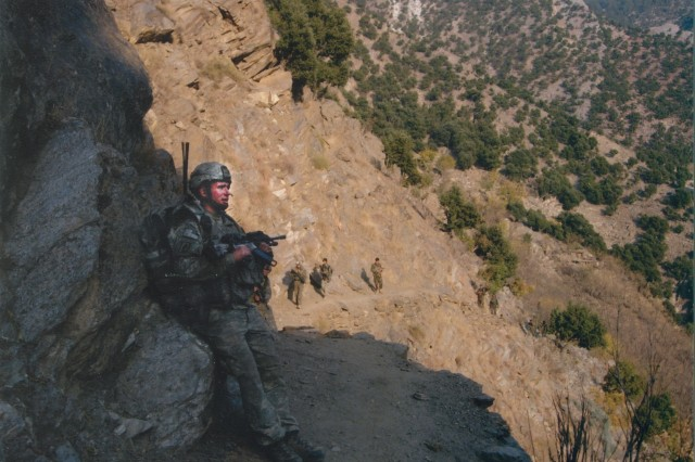 Spc. Kyle J. White resting from the 20-minute climb up the mountain to the trail home to Bella.
