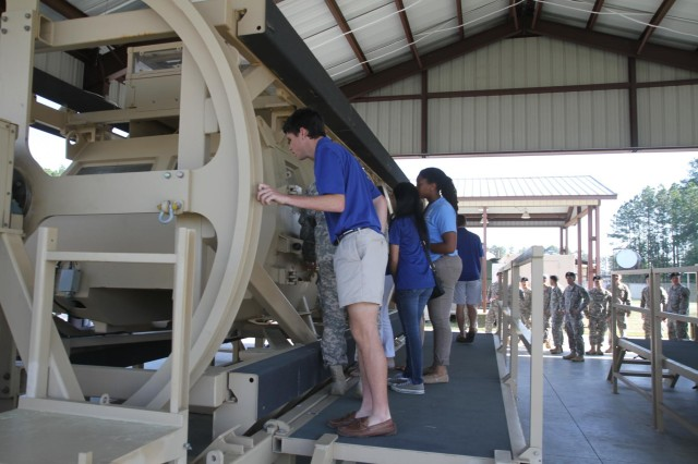 "Students from United Community Bank's Junior Board of Directors learn about a vehicle rollover simulator at Fort Stewart, Ga.'s ""virtual campus"" during a tour hosted by 3rd Battalion, 7th Infantry Regiment, 4th Infantry Brigade Combat Team, 3rd Infantry Division April 9, 2014.  (U.S. Army Photo by Sgt. Bob Yarbrough, 4th IBCT, 3rd ID, Public Affairs)"