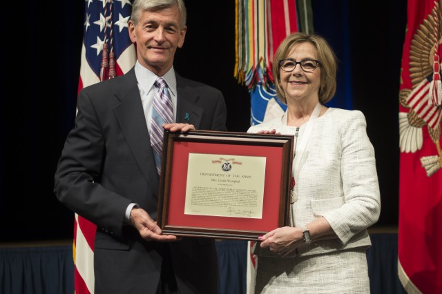 Secretary of the Army John McHugh presents Dr. Westphal's wife Linda with the Secretary of the Army Public Service Award for devoting many hours of work in support of Soldiers, civilians and their families and providing assistance to the Military Child Education Coalition, whose goal is to improve the education standards of Army families, April 14, 2014, Washington, D.C.