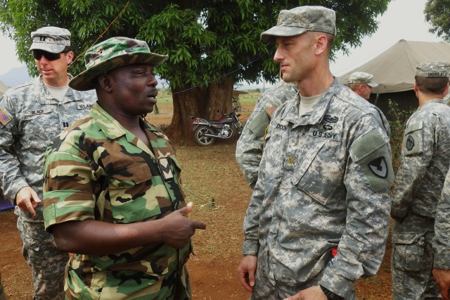 Nigerian Army Public Affairs Sgt. Mohammad Gongkie (left) talks with U.S. Army Maj. Brent Odom, RDECOM Field Assistance in Science and Technology advisor to U.S. Army Africa, before traveling to a local town for cultural day near Koutaba, Cameroon, during Central Accord 14, March 16.