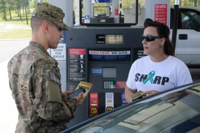 U.S. Army Staff Sgt. Kelley Archer (right), a Sexual Harassment and Assault Response Program representative with 5th Battalion, 25th Field Artillery Regiment, speaks with a Soldier at Fort Polk's main shoppette March 31, 2014, to help educate troops about the SHARP program. She and other volunteers spent the day educating Soldiers about National Sexual Assault Awareness Month. 5th Bn. is a part of 4th Brigade Combat Team, 10th Mountain Division.