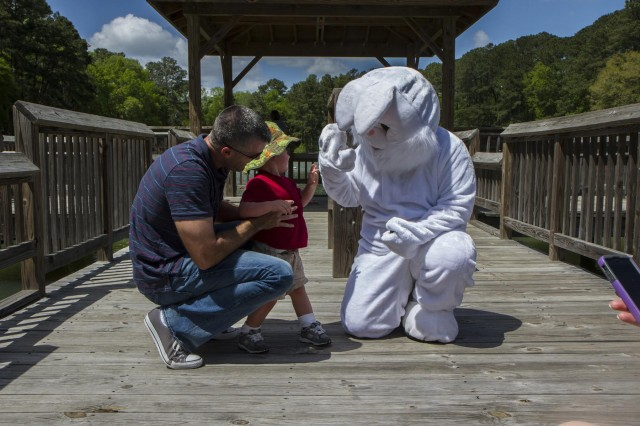 A young boy gives the Easter Bunny a high-five at the 3rd Combat Aviation Brigade Easter Egg Hunt at Hallstrom Lake recreation area on Hunter Army Airfield April 13. (Photo by Sgt. William Begley, 3rd CAB Public Affairs)