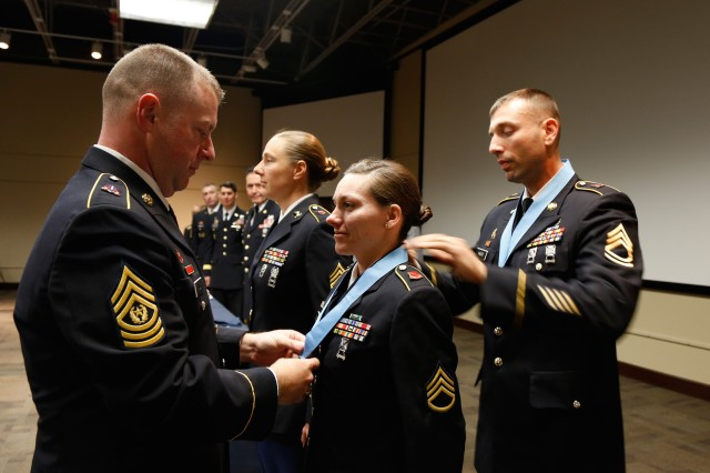 Command Sgt. Maj. James Wills, 80th Training Command (TASS) senior enlisted advisor, places the Sgt. Audie Murphy Club medallion around the neck of Staff Sgt. Kristina Fallis, 6/108th Regiment, 1st Brigade, 100th Training Division (Operations Support). Maj. Gen. Bill Gerety, commander, 80th TC, and Wills officially inducted Fallis into the prestigious SAMC during a ceremony at Fort Knox, Ky., in March 2014. (U.S. Army photo by Pfc. Jamill Ford/Released)