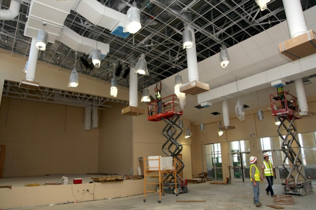 "Workers apply ceiling tiles inside a dual-space cafeteria and auditorium (called a ""cafetorium"") at the new Murray Elementary School. The room includes a built in stage."