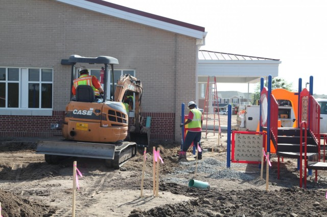 Workers prepare the ground for paving and landscaping surrounding a playground at the new Murray Elementary School. The school includes multiple playgrounds designed for children grades K-6.