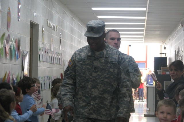 Students line the hall with American flags for the Soldiers from the Rock Island Chapter, Sgt. Audie Murphy Club, who delivered 79 computers to the school as part of the U.S. Army Computers for Learning Program. The program donates used and excess computers in the Army inventory to schools and non-profit organizations.