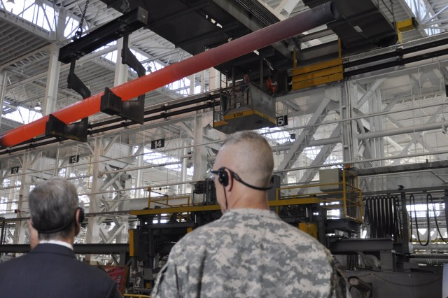 The Secretary of the Army John McHugh during a visit to the arsenal in September 2013, observes a 155-mm tube that was just forged, while Arsenal Commander Col. Lee H. Schiller looks on.