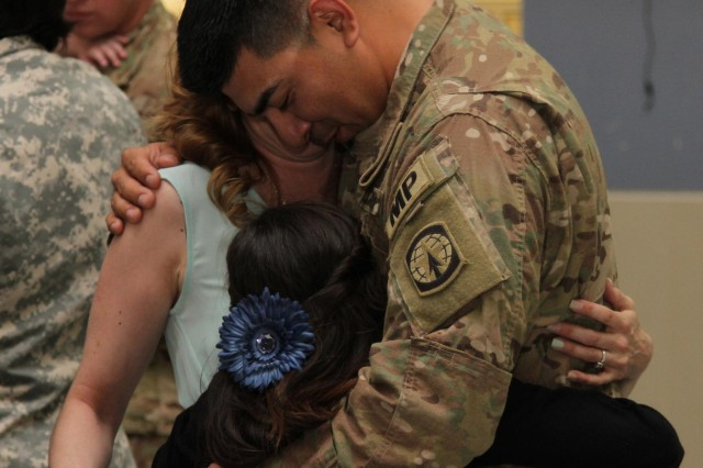 "Staff Sgt. John P. Martinez, a native of Elsa, Texas, and a Military Police with the 551st Military Police Company ""Hooligans,"" 716th Military Police Battalion, 101st Sustainment Brigade ""Lifeliners,"" 101st Airborne Division (Air Assault), greets his family with a big hug during a welcome home ceremony April, 10 at Fort Campbell. The Hooligans were deployed in Afghanistan for nine months where they proudly served their country with honor conducting customs missions. (U.S. Army photo by Sgt. Sinthia Rosario, 101st Sustainment Brigade Public Affairs)"