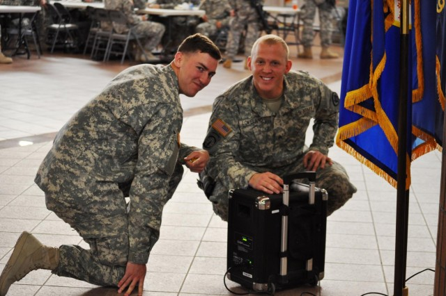 Soldiers of the 420th Military Police Company, 508th Military Police Battalion, a Reserve unit from Salt Lake City, Utah, serve as impromptu deejays prior to the unit's departure from the Arrival/Departure Air Control Group, here, April 8. Spc. Logan M. Scott, from Powdersville, S.C. (left) and Sgt. Dustin C. Loveland, from Cedar City, Utah, boost morale for their unit before deploying to Guantanamo Bay, Cuba, to conduct detainee operations.
