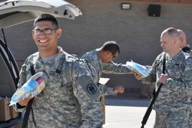 Soldiers of the 420th Military Police Company, 508th Military Police Battalion, a Reserve unit from Salt Lake City, Utah, receive care packages prior to boarding a plane at the Arrival/Departure Air Control Group, here, April 8. The 420th MP Company deployed to Guantanamo Bay, Cuba, to conduct detainee operations.