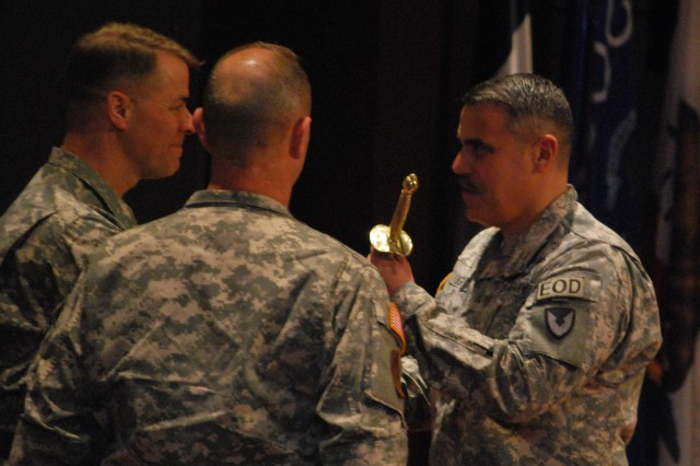 Brig. Gen. Ted Harrison passes a ceremonial sword representing the responsibilities of the command's senior noncommissioned officer to Command Sgt. Maj. David M. Puig during the Army Contracting Command's change of responsibility ceremony April 17.
