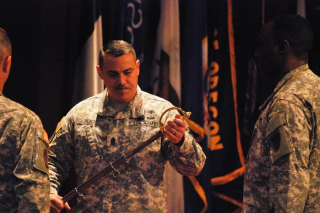 Command Sgt. Maj. David M. Puig, the Army Contracting Command's new command sergeant major, looks at the ceremonial sword during the change of responsibility ceremony April 17.