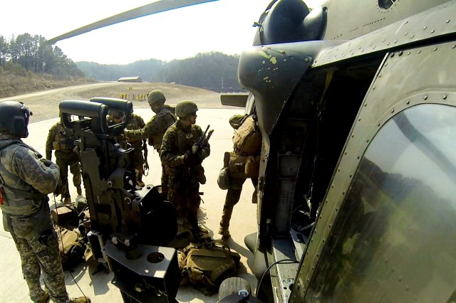 2nd Combat Aviation Brigade Soldiers prepare their weapon system before air assaulting Republic of Korea and U.S. Marines from a UH-60 Blackhawk helicopter, March 13, 2014 in South Korea.  (Photo courtesy of Mikkel Thomas)