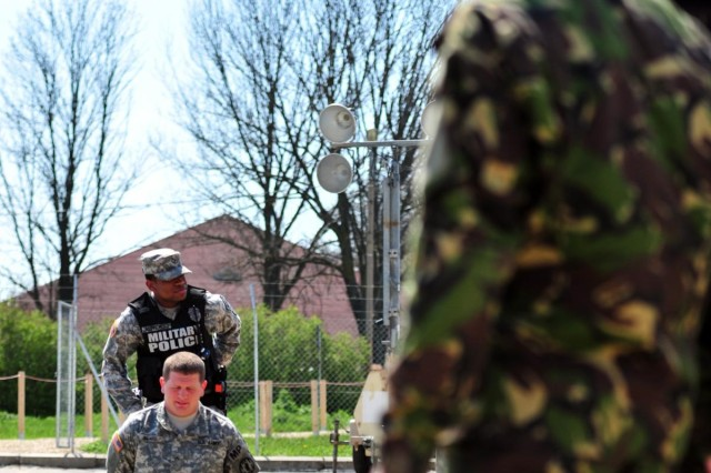 A Romanian soldier watches as Pfc. Tyheem A. Alphonso, a military policeman assigned to the 202nd Military Police Company, 93rd Military Police Battalion, 89th Military Police Brigade and a native of Brooklyn, N.Y., demonstrates how to hand-cuff a perpetrator on Pvt. Andy Beard, also a military policeman assigned to the 202nd MP Co. and a native of Evansville, Ind., during combined training at the Mihail Kogalniceanu Airbase passenger Terminal April 15. The training is in preparation for U.S. and Romanian combined military police patrols set to begin on MK Airbase in the near future. (Photo by Staff Sgt. Alexander Burnett, 21st TSC Public Affairs)