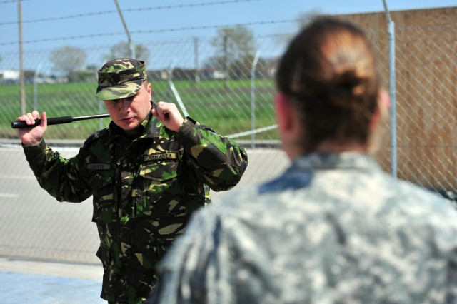 A Romanian military policeman practices swinging an Asp baton while being coached by Pfc. Neka J. Hartwell, a military police Soldier assigned to the 202nd Military Police Company, 93rd Military Police Battalion, 89th Military Police Brigade and a native of Naples, Fla., during during combined training at the Mihail Kogalniceanu Airbase passenger Terminal April 15. The training is in preparation for U.S. and Romanian combined military police patrols set to begin on MK Airbase in the near future. (Photo by Staff Sgt. Alexander Burnett, 21st TSC Public Affairs)