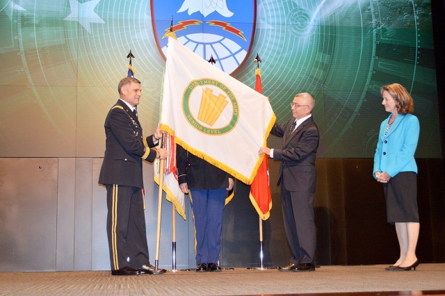 Lt. Gen. David L. Mann, commanding general, U.S. Army Space and Missile Defense Command/Army Forces Strategic Command, presents Dr. Steve F. Pierce, SMDC's chief technology officer, with a senior level flag during Pierce's promotion ceremony April 17 at the Von Braun III auditorium. Pierce's wife, Debora, watches.